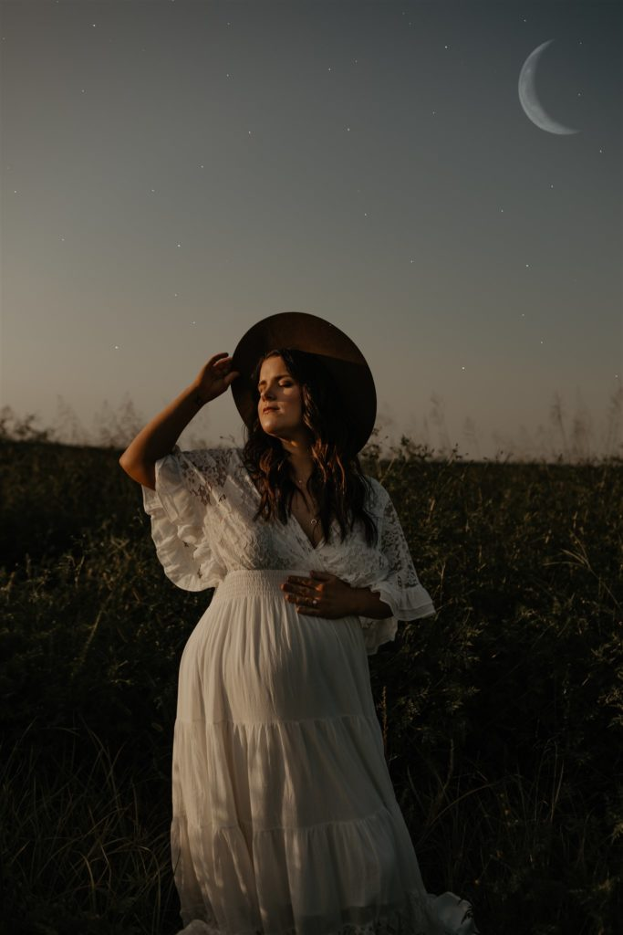 Serene pregnant woman in sunset field with the moon in the background. She has a hand on her belly and on her hat brim