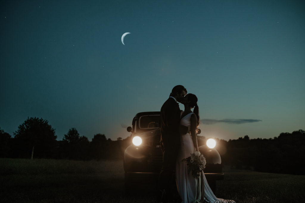 Dusk picture of bride and groom kissing in front of the hood of the vintage pick up. Its headlights are on and a crescent moon in the sky